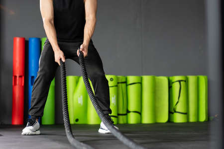 Strong Asian sportive man standing in a ready position for doing a battle rope exercise in a indoor gym with copyspace. Powerful young sportsman training a body building concept, muscle building.