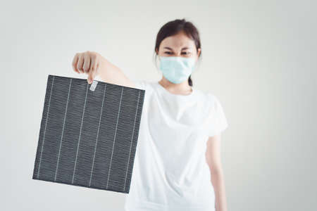 Asian woman wearing a hygiene protective face mask during changing a dirty air filter in the air purifier machine close up with copyspace. Hygienic lifestyle and prevention from illness concept. 免版税图像