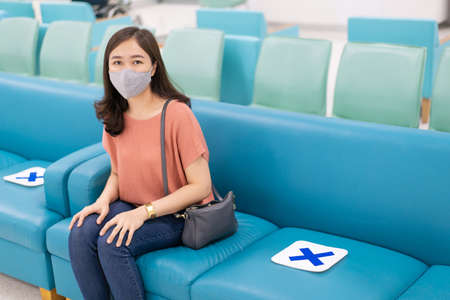 Asian woman with hygiene protective face mask over her face sitting on a sofa seat in the hospital with a social distancing protocol while COVID-19 or Coronavirus outbreak. Using face mask concept.