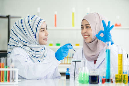 Happy Asian muslim scientist student investigating a chemistry together in laboratory. Two intelligence Muslim chemistry researcher examining and testing for pharmaceutical chemistry. Bio tech concept 免版税图像