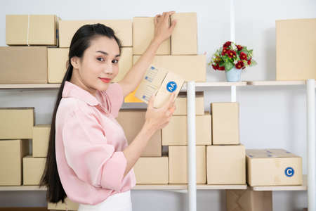 Asian beautiful woman picking up a parcel box from shelves. Online woman vendor and e-commerce concept.