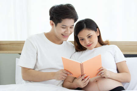 Portrait of lovely husband and wife reading a book together on the bed in bedroom, husband embracing his pregnant wife on a bed during reading a book. Couple relaxing together. Family leisure activity 免版税图像