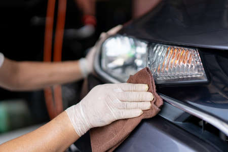 Asian workman wiping a car's headlight with high quality microfiber cloth in garage. Professional car care workshop. 免版税图像
