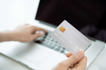 unrecognizable woman holding a credit card in front of the laptop computer screen, Online shopping and secure online payment concept. 免版税图像