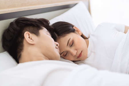 Lovely husband and wife sleeping together on the bed in bedroom close up. Husband embracing his pregnant wife with affectionate love. Closeness of Asian couple ethnicity portrait. 免版税图像