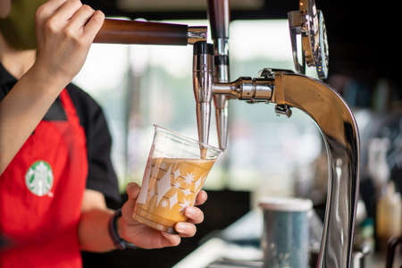 Nonthaburi - Thailand November 22, 2020: Professional Starbucks's barista pouring a Nitro Cold Brew coffee from the Nitro Cold Brew machine tap into a Starbucks plastic cup close up.