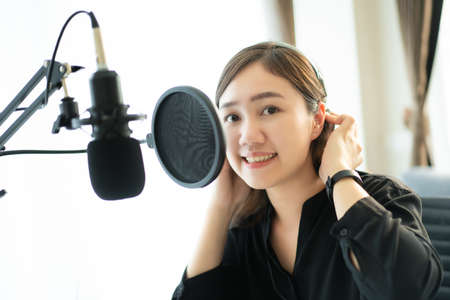 Happy Asian woman setting up a living room in her house for podcast studio, woman arranging a podcast and online radio station at home. Professional young podcaster speaking through a microphone.