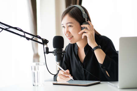 Beautiful and good looking young Asian woman arranging home podcast channel. Businesswoman recording her podcast for her online podcast live on the laptop computer and tablet. Modern working lifestyle