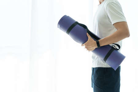 Unrecognizable Asian young man carrying a roll of yoga mat preparing for exercise or workout. Man making an exercise at home by himself. Sportive man holding a exercise or yoga mat close up.