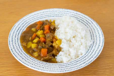 Home made Japanese beef curry served with Japanese rice in a plate close up. Japanese beef curry is one of the most favorite dish of Japan. Imagens