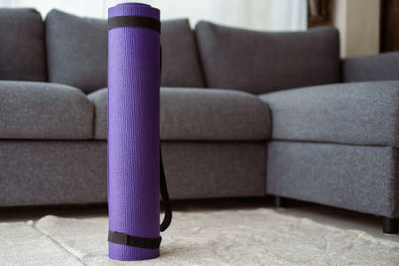 Rolled purple yoga exercise mat on the floor in living room close up with copyspace. Indoor workout activity concept. Rolling Purple Yoga carpet close up. Imagens