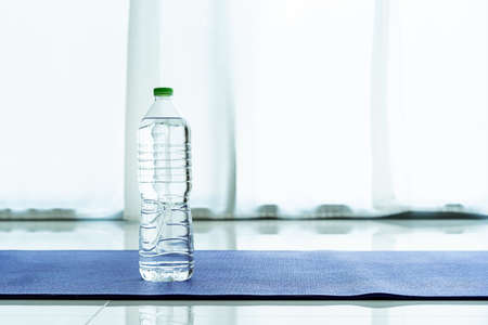 Bottle of drinking water on the purple yoga mat in the living room, home exercise concept. Workout at home equipment.