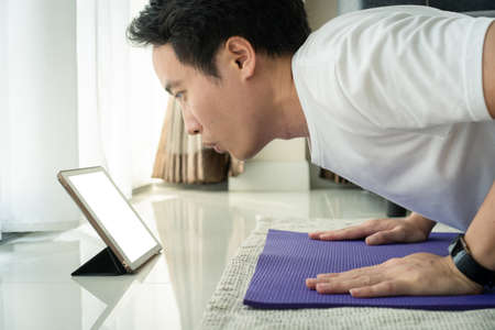 Young Asian young man doing a plank and push up exercise and watching on a tablet, tablet isolated screen in white with clipping path. Man learning and training an exercise online on tablet.