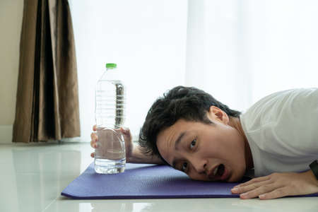 Funny tired face of Asian young man laying down on the floor and trying to grab a water in bottle. Man tired from hard workout.