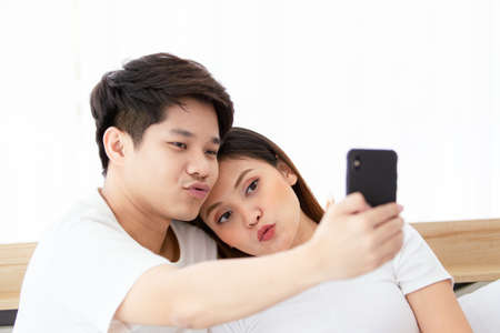 Happy Asian young couple enjoy taking a selfie photography on the bed in bedroom, cheerful Asian husband and wife living together in bedroom. Couple using smartphone to take a selfie photo.