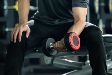 Asian young man practice weight training workout in the gym, body building exercise. Muscle building challenge concept. Strong sportsman lift up a dumbbell close up with copyspace.
