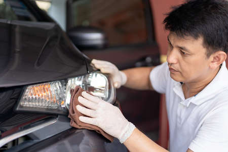 Asian man using a soft microfibre wiping and cleaning car exterior at the headlight close up. Car care service concept with copyspace. 免版税图像