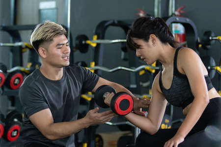 Weight training instructor train the beginner apprentice for muscle building. Fitness personal trainer advise a woman for physical workout.