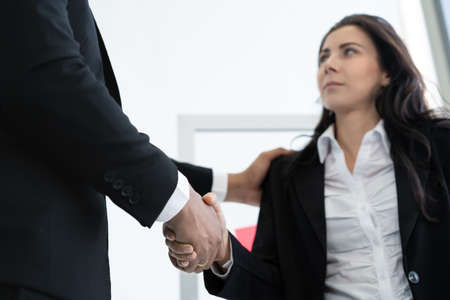Asian and caucasian ethnicity businesspeople doing a handshake together after done and completed business negotiation. Trust in business partnership and colleague. Successful in business concept 免版税图像