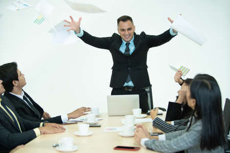 Aggressive businesspeople in meeting, the angry boss throwing a paperwork in the air during business meeting. Depressed and conflict business conference concept. Boss shouting at employees.