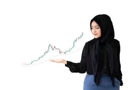 Beautiful Asian young muslim woman standing on the bright yellow background and showing right hand on the space for text in copy space. Satisfaction and trust concept. Diversity business formal. 免版税图像