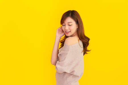 Beautiful Asian young woman's portrait on bright yellow background, Studio portrait of Asian girl showing her beautiful shoulder and smile to camera with copyspace. Pretty Asia girl  happy posing.