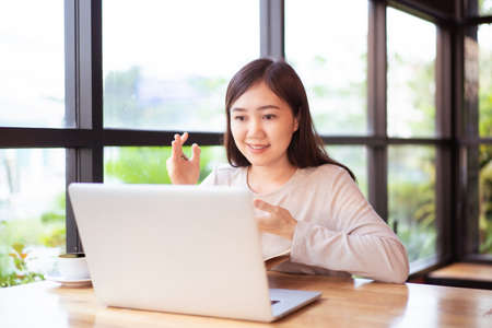 Asian happy woman working in coffee shop or co-working space on laptop computer, online working and online video conference concept in modern working lifestyle. Asian businesswoman smiling portrait.