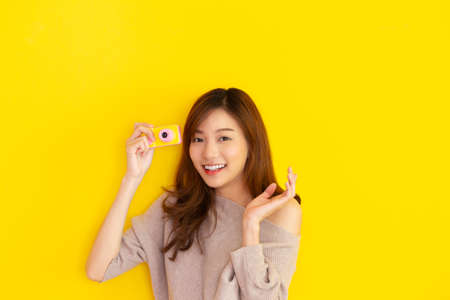 Cheerful Asian woman traveler posing for a photography on yellow background and showing a vintage small toy camera, happy Asian tourist in tourism concept with copy space, girl traveler smiling.