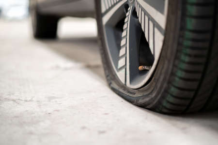 Close up photograph of damaged wheel - flat tire of an accident vehicle. A car have an accident on a wheel.