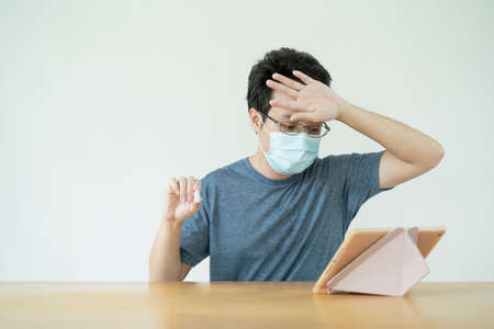 Asian young man showing the COVID-19 or Coronavirus antigen - ag testing result to a doctor in the online video call, tele - online medication service. Reklamní fotografie