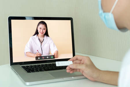 Unrecognizable Asian young man having a health problem and consulting with doctor via online medication service. Man got a COVID-19 disease and chat to doctor on a video call on laptop.