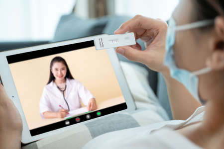 Asian young woman with hygiene protective face mask using SARS 2019-nCoV COVID-19 coronavirus antigen rapid test kit - ag test kit at home and consulting a testing result with doctor via video call. Reklamní fotografie