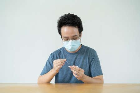 Asian young man having a swab COVID-19 or Coronavirus 2019 antigen - ag self test at home. Antigen or ag test use for 2019 SARS nCoV infection test. Reklamní fotografie