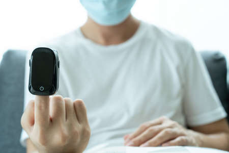 Man using oximeter to measure his blood oxygen saturation and pulse. Digital portable blood oxygen meter.