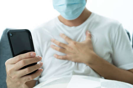 Unrecognizable Asian young man with face mask having a health problem and consulting with doctor via online medication service. Man got a COVID-19 disease and chat to doctor on a video call. Reklamní fotografie