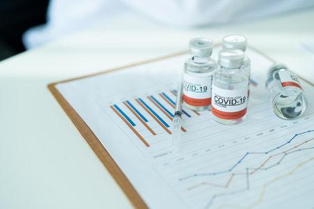 COVID-19 or coronavirus cure vaccine analysis in statistics report concept. Copy space in photo. COVID19 vacination report.