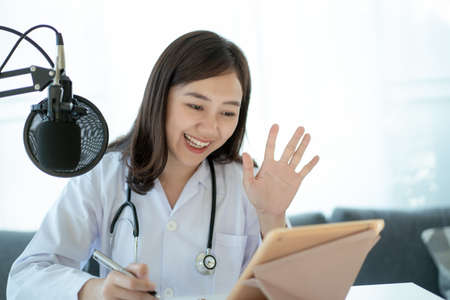 Asian doctor making an online video conference with her patient, tele medical service concept. Female doctor making a medication advise via online podcast.