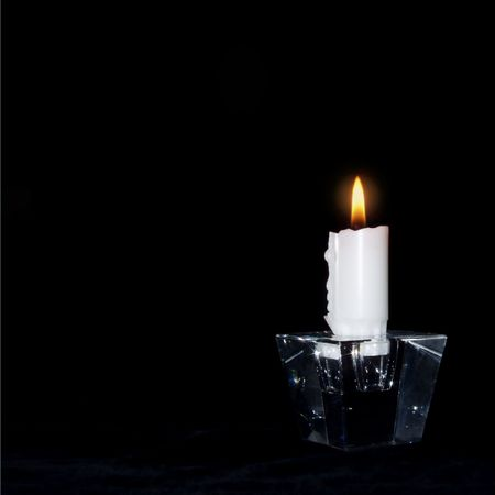 Candle in the dark lit for: peace, love, understanding, the world, you and me photo
