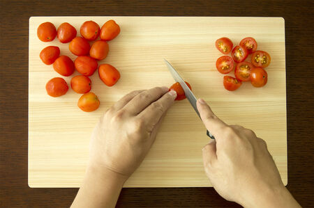 First Person View Chopping Cherry Tomato on Cutting Board