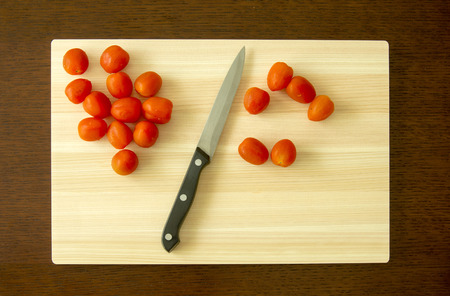 Cherry Tomato and knife on cutting board