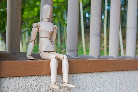wood carving 3d: Wooden  figure sitting on architrave window and selective focus Stock Photo