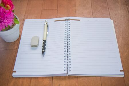 Blank space of notepad with supplies and flower. Top view with copy space Stock Photo