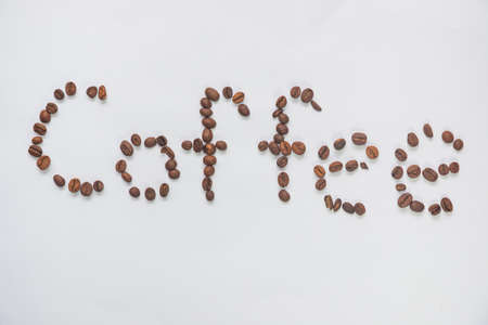 caf: Inscription coffee from coffee grains on a white background