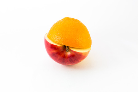 genetically modified organisms: Creative apple combined from red apple and orange half isolated on white. Concept