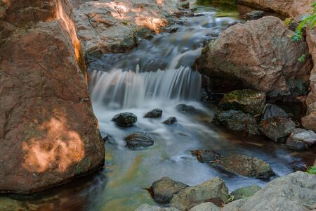 jumble: Water falls over a jumble of moss-covered boulders in forest.