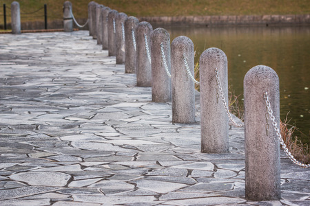 lined up: Stone pole and chain fence, prevent falling into water.