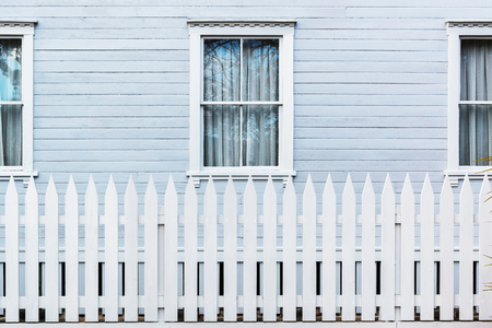 country house style: White wooden country style fence with windows of house at behind