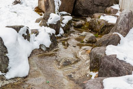 water frozen: Watercourse over stone in winter with snow. Stock Photo