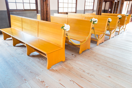 pews: church interior with empty a row of wooden pews.