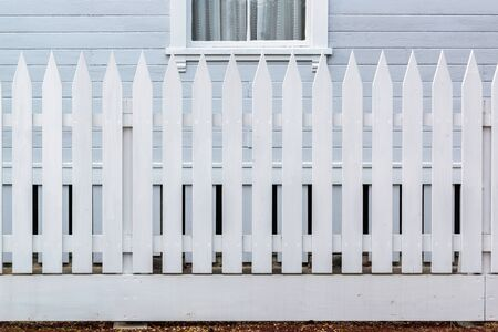 country house style: White wooden country style fence with wall of house Stock Photo